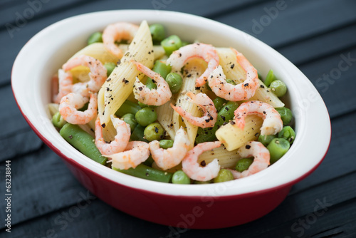Penne with shrimps, peas and beans, black wooden background