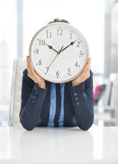 Happy business woman holding clock in front of face