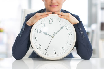 Closeup on business woman with clock