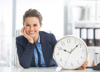 Happy business woman showing clock