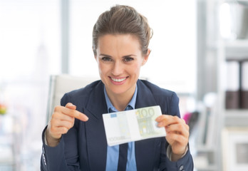 Happy business woman pointing on money pack