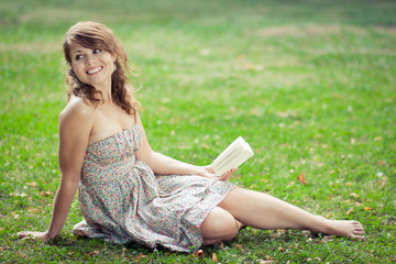 Beautiful young woman reading a book outdoors