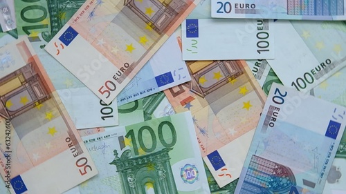 A lot of euro banknotes are rotated on table.