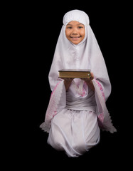 Young Asian Muslim girl in white hijab with Al Quran