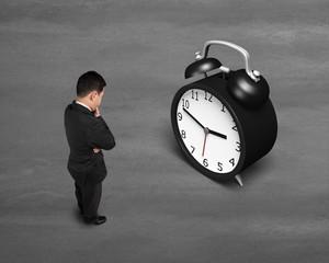 Businessman face alarm clock