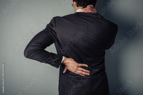 Businessman with sore back and neck