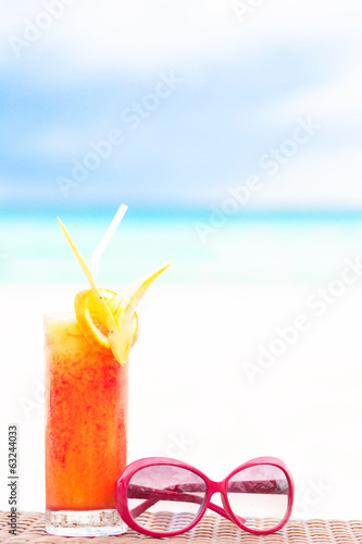 fresh fruit cocktail with sunglasses on tropical beach