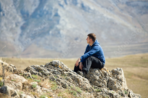 Man relaxing on top of mountain