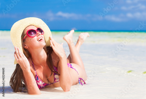 long haired girl in bikini and sunglasses on tropical beach in