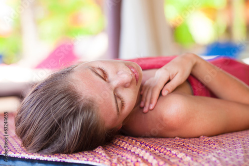 portrait of beautiful young woman with lying in spa