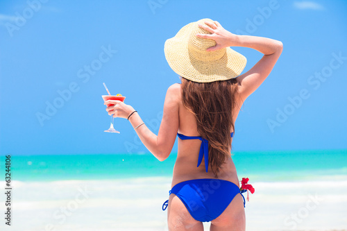 closeup back view young long haired woman in blue bikini with