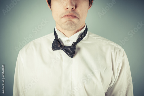 Sad young man with messy bow tie