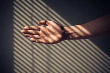 Man's hand with shadows from blinds
