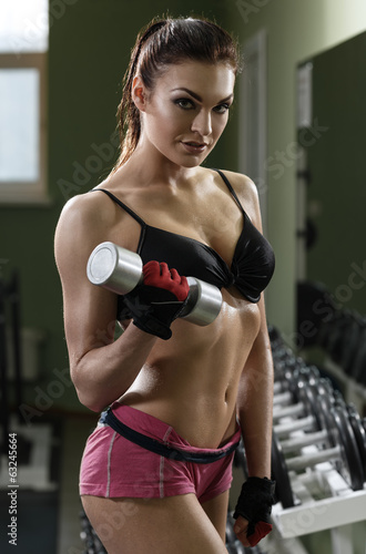 Woman bodybuilder training with dumbbell