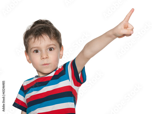 Surprised little boy shows his finger aside