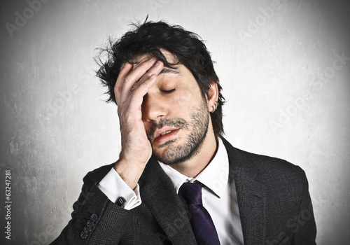 Stressed businessman with hand on the head