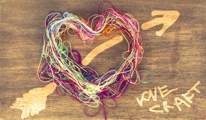 love craft thread heart on the wooden background