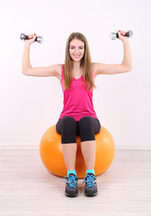 Young beautiful fitness girl exercising with orange ball and