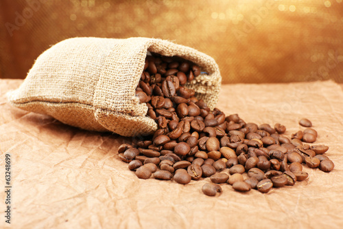 Coffee beans in sack on table close-up