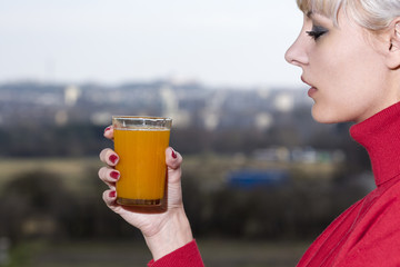 Young woman holds in hand a glass with juice