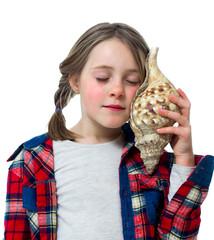 Little girl listening a shell