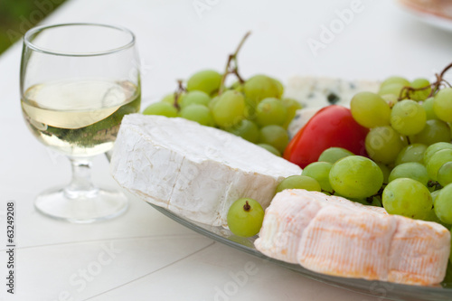 Various sorts of cheese, grapes and glass of the white wine