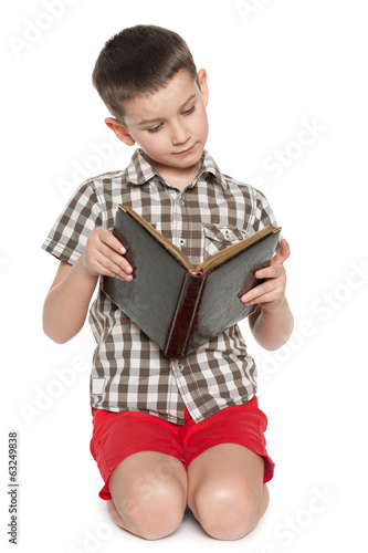 Young boy reads an old book