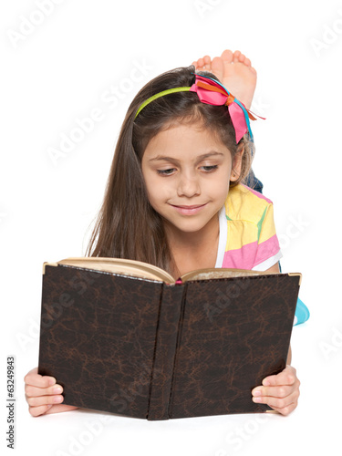 Smiling little girl reads an old book