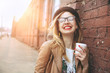 Cheerful woman in the street drinking morning coffee in sunshine