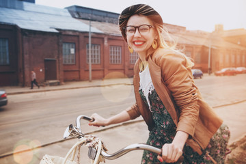 stylish woman riding on bike in morning sunshine