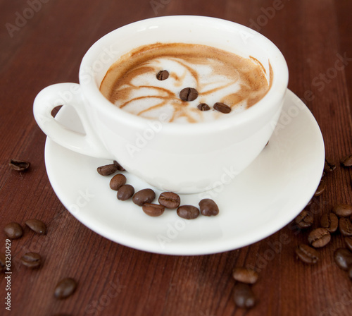 A cup of cappuccino and coffee beans
