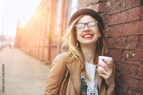 Leinwanddruck Bild Cheerful woman in the street drinking morning coffee in sunshine
