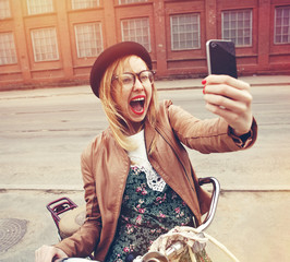 City lifestyle stylish hipster girl with bike using a smartphone