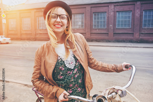 Cheerful  woman with bike in morning sunshine