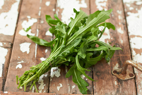 Bunch of fresh arugula leaves on a wooden table