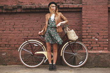 fashionable woman with vintage bike on brick wall background