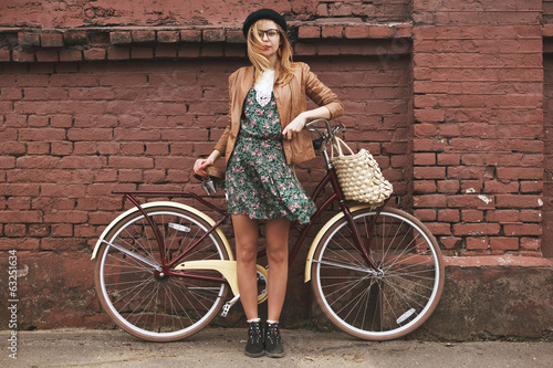 Aluminium Wielersport fashionable woman with vintage bike on brick wall background