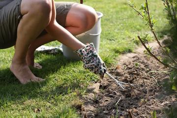 Frau mit Harke und buntem Handschuh, Garten