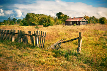 Old house with wooden fence on the empty meadow