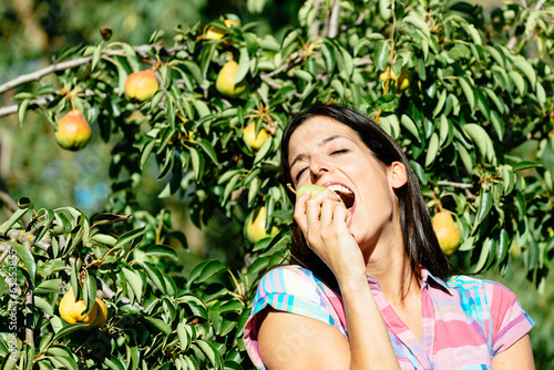 Female farmer eating fruit from pear tree
