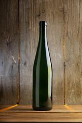 Weinflasche vor Holzwand mit atmosphärischer Beleuchtung