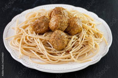 meatballs with spaghetti in white plate on black background