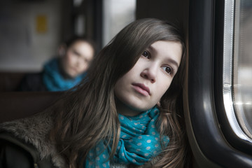 teenager girl sitting in the carriage looking through the window