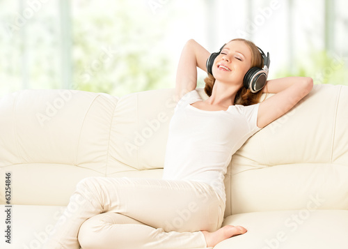 beautiful girl in headphones enjoying music at home