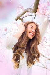 Junge hübsche Frau im Kirschbaum