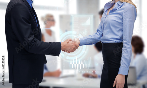 man and woman shaking their hands in office