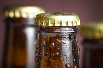 closeup of top of bottle of fresh beer with drops
