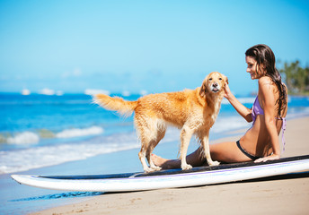 Young Woman Enjoying Sunny Day at the Beach with her Dog