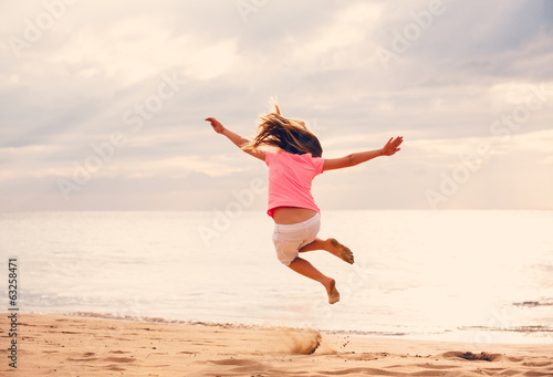 Happy Girl Jumping on the Beach at Sunset