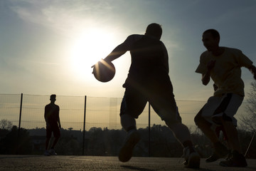 Basketball player silhouettes playing outdoors